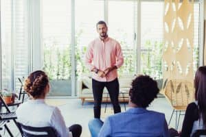 Confident male speaker holding seminar. Young entrepreneur in casual speaking before audience. Business training concept
